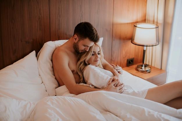 Piękna para przytulanie na swoim łóżku w domu