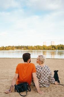 Piękna para relaksując się na piasku, przytulanie i całowanie podczas zabawy z pozytywnym psem