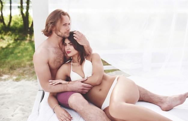Piękna para relaksująca się na piaszczystej plaży, ubrana w strój kąpielowy. romantyczna atmosfera