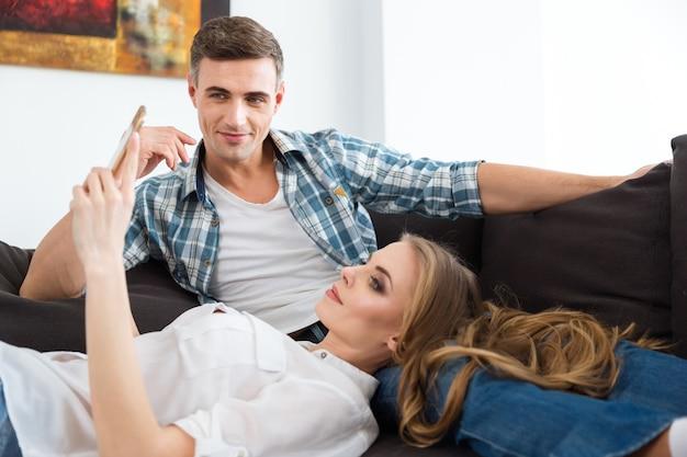 Piękna para relaksuje się na kanapie i używa telefonu komórkowego w domu