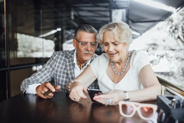 Piękna para seniorów szuka czegoś w telefonie, siedząc na letnim tarasie w nowoczesnej kawiarni