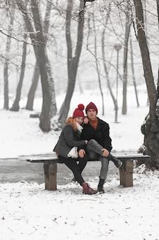 Piękna para siedzi na ławce długi widok