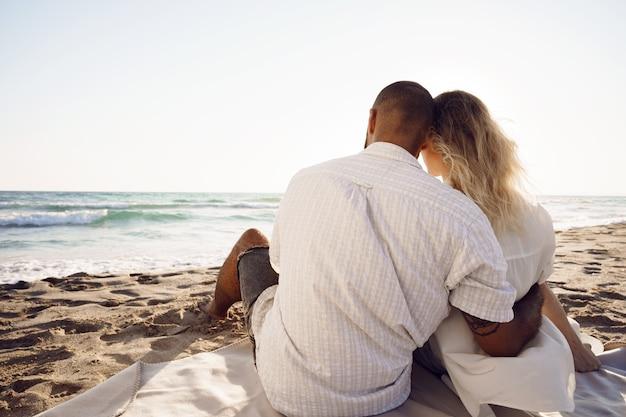 Piękna para siedzi na plaży i ogląda zachód słońca
