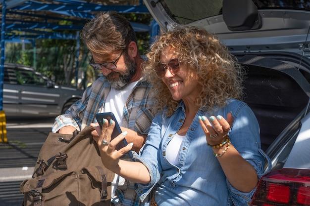 Piękna para siedzi na zewnątrz na parkingu za pomocą smartfona i uśmiechnięty. kręcona blondynka i brodaty mężczyzna