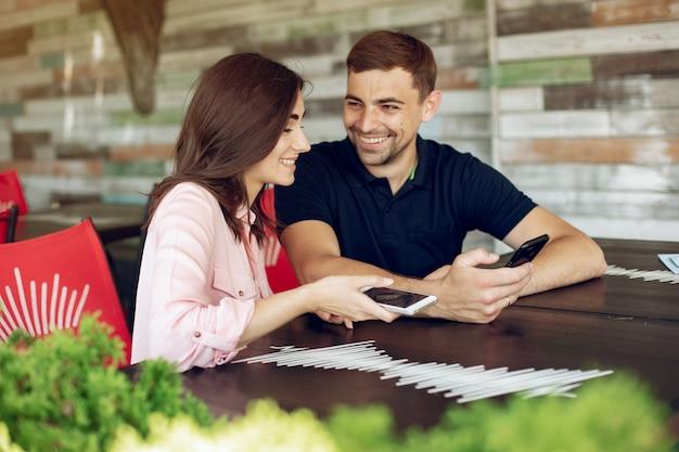 Piękna para siedzi w letniej kawiarni