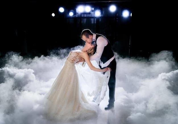 Piękna para ślub stoi w dymie podczas ich pierwszego tańca