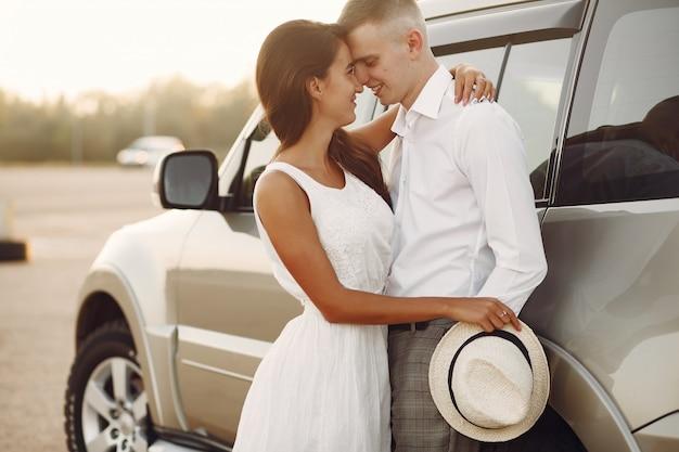 Piękna para spędza czas w letnim parku w pobliżu samochodu