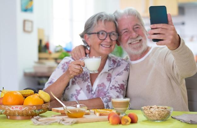 Piękna para starszych jedząca śniadanie w domu, patrząca razem na telefon komórkowy, aby zrobić selfie