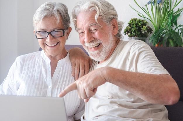 Piękna para starszych przy użyciu komputera przenośnego śmiejąc się. spokojni starsi ludzie korzystający z technologii i społeczności