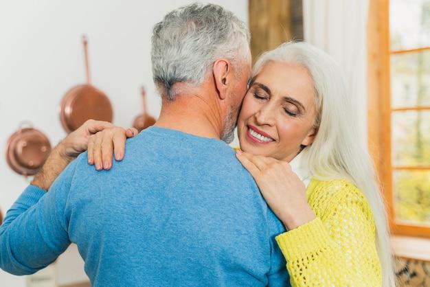 Piękna para starszych tańczy w domu.