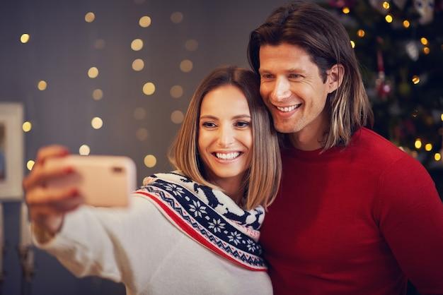 Piękna para świętująca boże narodzenie w domu i robiąca selfie