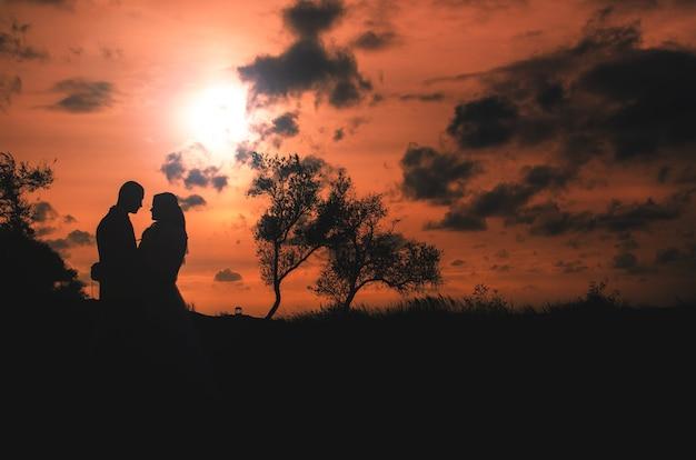 Piękna para sylwetek na tle zachodu słońca jest bardzo piękna i wzruszająca