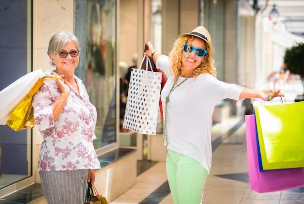 Piękna para szczęśliwych kobiet posiadających torby na zakupy w centrum handlowym. koncepcja konsumpcjonizmu