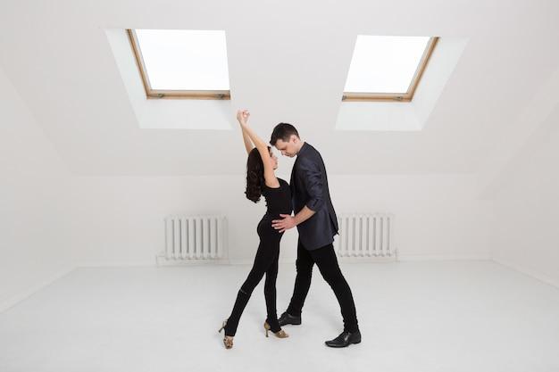Piękna para tańczy bachata na białym tle w studio