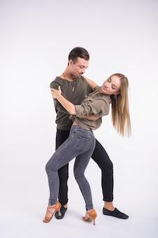 Piękna para tańczy taniec towarzyski. kizomba lub bachata lub semba lub taraxia, na białym tle. koncepcja tańca społecznego.