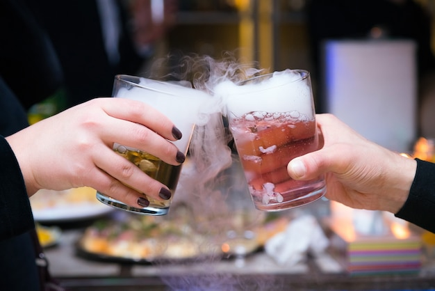 Piękna para trzyma koktajle z suchego lodu na imprezie.