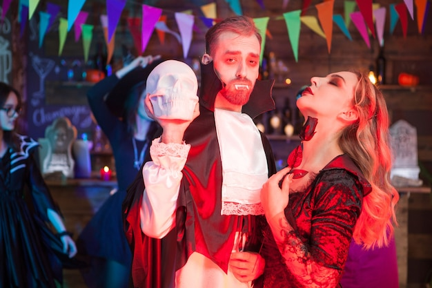 Piękna para ubrana jak dracula i seksowna wiedźma na przyjęcie z okazji halloween. dracula trzyma straszną czaszkę.