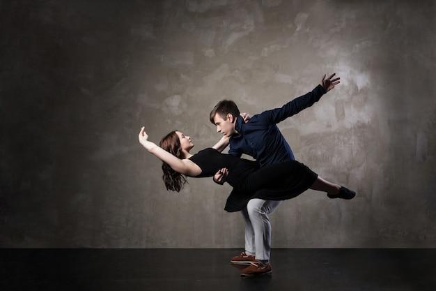 Piękna para w aktywnym tańcu towarzyskim na ciemnym tle