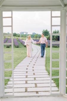 Piękna para w średnim wieku, przystojny mężczyzna i urocza kobieta, chodzą trzymając się za ręce po ścieżce