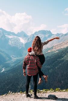 Piękna para wśród gór. zakochana para w górach, widok z tyłu. mężczyzna wziął kobietę w ramiona. para podróżuje wśród gór. piesze wycieczki po górach. skopiuj miejsce