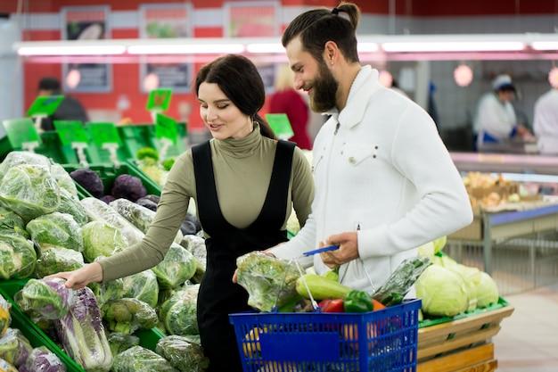 Piękna para wybiera kapustę w supermarkecie