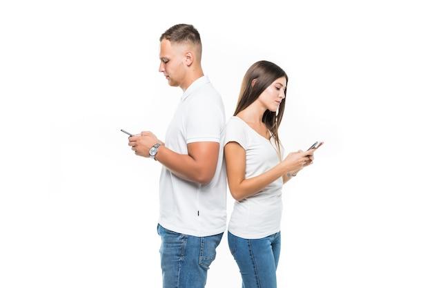 Piękna para z telefonów komórkowych, pozostając plecami do siebie na białym tle