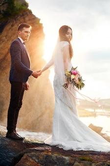 Piękna para zakochanych całuje stojąc na skałach nad morzem