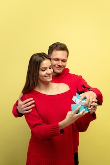 Piękna para zakochanych, otwierając prezent na żółtej ścianie studio
