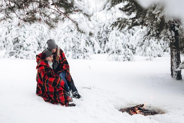 Piękna para zakochanych siedzi przy ognisku w śnieżnym lesie zimą przykryta kocem
