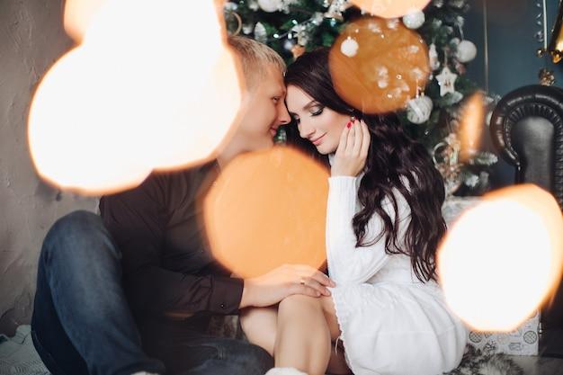 Piękna para zakochanych świętuje razem nowy rok. obraz ze światłami makro