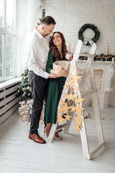 Piękna para zakochanych zabawy, święta i nowy rok w domu. młoda rodzina razem.