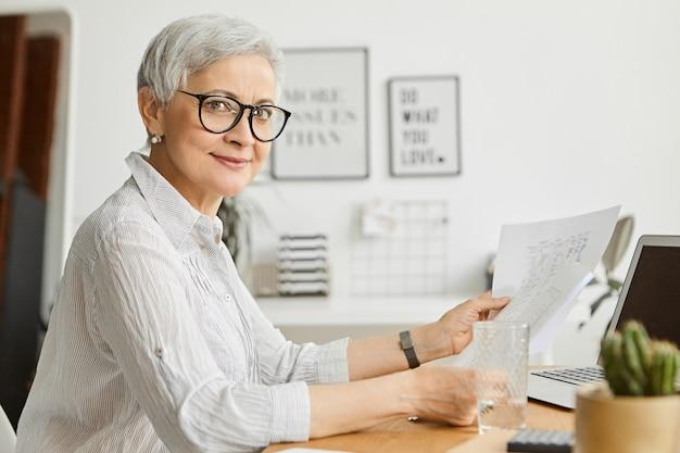 Piękna pewna siebie, odnosząca sukcesy kobieta z krótkimi siwymi włosami pracująca w biurze, przy użyciu przenośnego komputera trzymającego w rękach papiery, studiująca sprawozdanie finansowe, uśmiechnięta