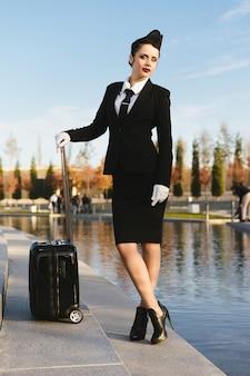Piękna pewna siebie stewardessa w mundurze pozowanie, z walizką
