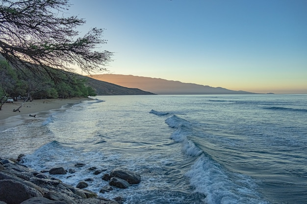 Piękna piaszczysta plaża z błękitnym morzem i niebem