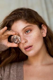 Piękna piegowata kobieta zasłaniająca oko przezroczystym kryształem