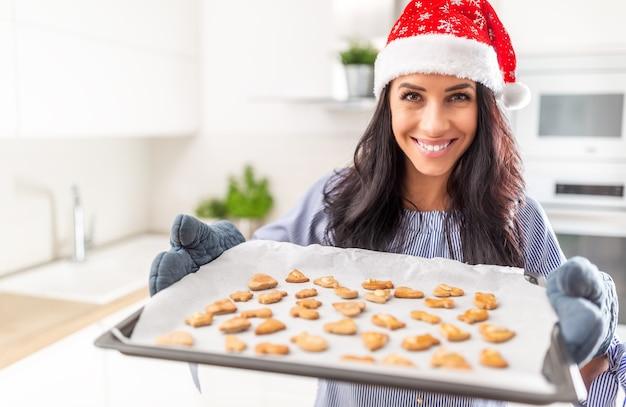Piękna piekarz w świątecznym kapeluszu pokazuje jej pracę. smaczne pierniczki na papierze do pieczenia.