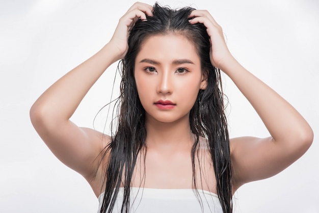 Piękna, piękna kobieta łapie swoje rozczochrane włosy.