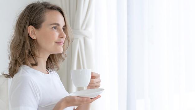 Piękna piękna kobieta śliczna dziewczyna czuje się szczęśliwy, pijąc kawę rano