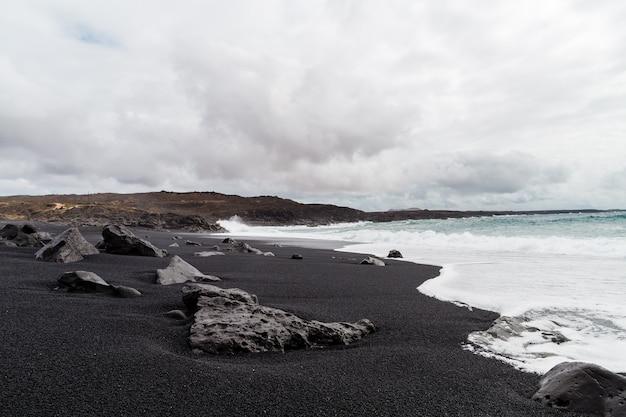 Piękna plaża na wyspie lanzarote. piaszczysta plaża otoczona wulkanicznymi górami / oceanem atlantyckim i cudowna plaża. lanzarote. wyspy kanaryjskie