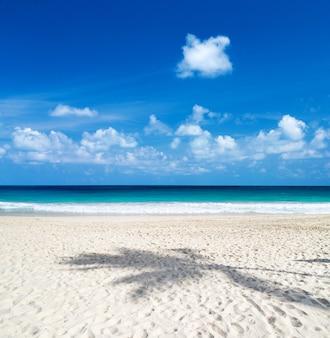 Piękna plaża z białym piaskiem. tropikalne morze z chmurnym niebieskim niebem. niesamowity krajobraz plaży
