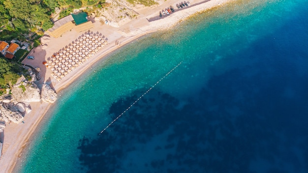 Piękna plaża z krystalicznie czystą wodą na morzu śródziemnym. widok z lotu ptaka. słoneczny dzień.