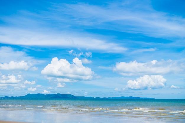 Piękna plaża z morzem i oceanem na niebieskim niebie