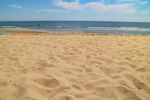 Piękna plaża z piaskiem, fala i niebieskim niebem w lato czasie