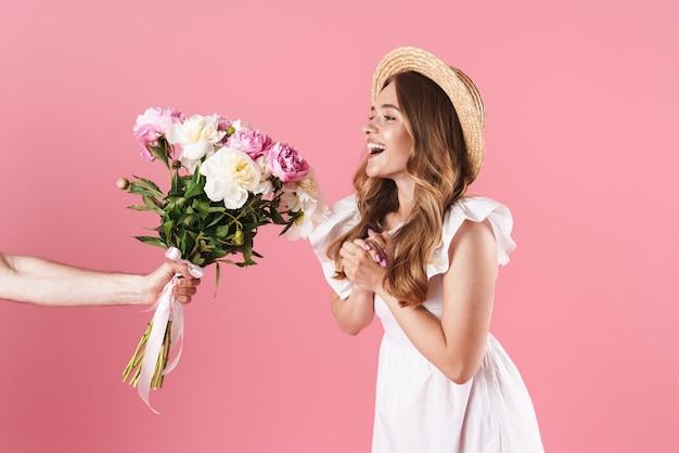 Piękna podekscytowana młoda blondynka ubrana w letnią sukienkę stojącą na białym tle nad różową ścianą, otrzymująca w prezencie bukiet piwonii