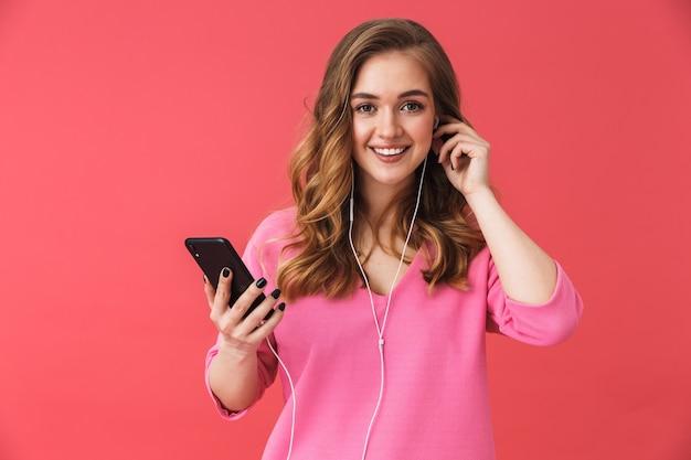 Piękna podekscytowana młoda dziewczyna w zwykłych ubraniach, stojąca na białym tle nad różową ścianą, słuchająca muzyki przez słuchawki, trzymająca telefon komórkowy