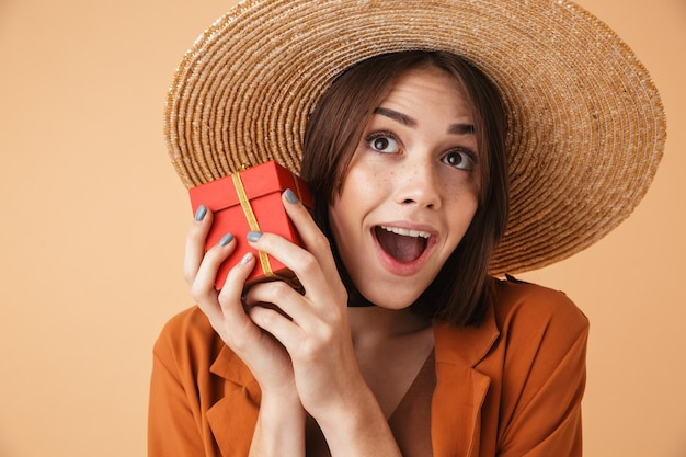 Piękna podekscytowana młoda kobieta w słomkowym kapeluszu i letnim stroju stojąca na białym tle nad beżową ścianą, trzymająca pudełko na prezent