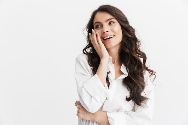 Piękna podekscytowana młoda kobieta z długimi kręconymi włosami brunetki, ubrana w białą koszulę, stojąca na białym tle nad białą ścianą, odwracająca wzrok