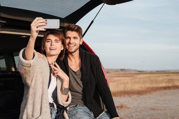 Piękna podekscytowana para robi selfie siedząc w samochodzie nad morzem