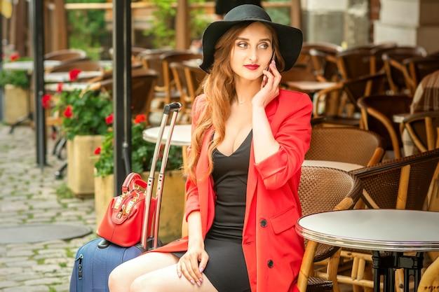 Piękna podróż młoda kobieta kaukaski rozmawia przez telefon, siedząc w kawiarni na świeżym powietrzu