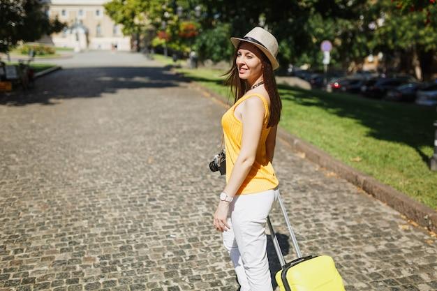 Piękna podróżniczka turystyczna kobieta w żółte letnie ubrania dorywczo, kapelusz z walizką spaceru w mieście na świeżym powietrzu. dziewczyna wyjeżdża za granicę na weekendowy wypad. koncepcja życia podróż turystyka.
